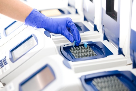 chain reaction: Scientist with DNA copying, Real-time PCR cycler, wide Stock Photo
