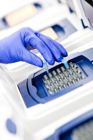 角度のついた: DNA 複製、リアルタイム PCR サーマルサイクラーを持つ科学者の角度