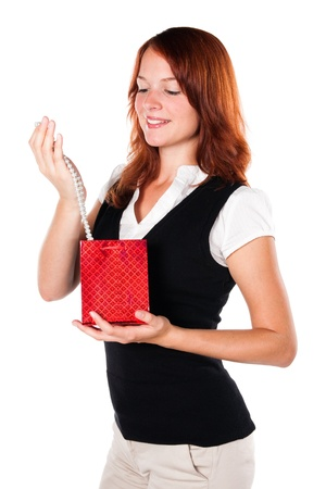 zoomed in: Beautiful woman is looking at her new gift - necklace - in a red box. Zoomed out version.