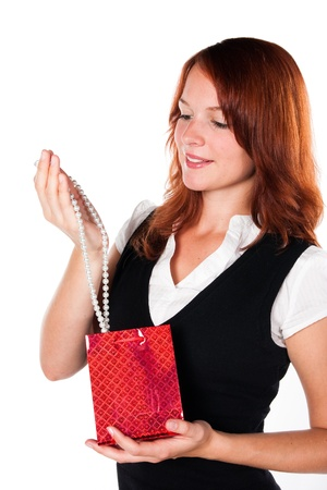 zoomed in: Beautiful woman is looking at her new gift - necklace - in a red box. Zoomed in version. Stock Photo