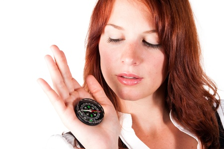 Beautiful red-headed girl is holding a compass near her face. The compass is pointing to the north. photo