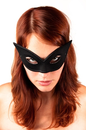 Beautiful red-headed girl in black mask looking straight to the camera. Corrected color. photo