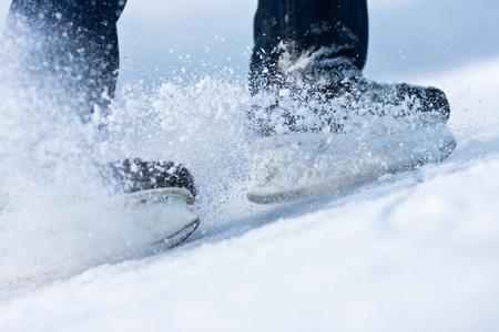 patinar: Dos patines para romper el hielo con la nieve volando Foto de archivo