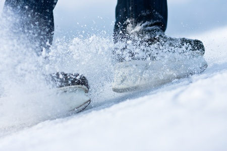 hockey skates: Two breaking ice skates with flying snow