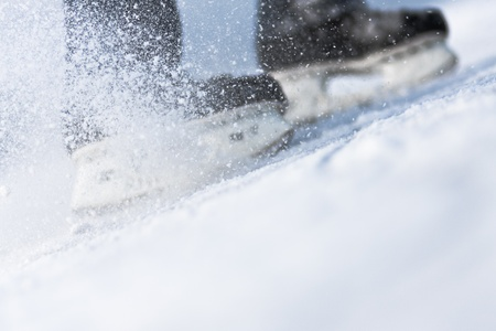 ice hockey: Snow flying from braking, ice skates blurred Stock Photo