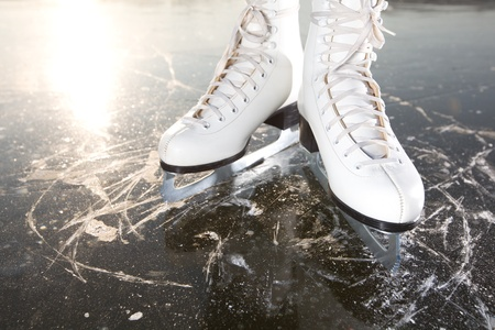 figure skates: Wide skates on ice with sun reflected in behind