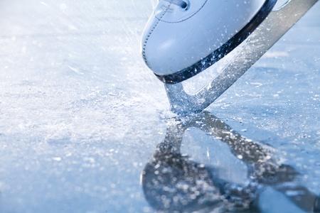 skating: Woman skates braking ice, frazil flying around