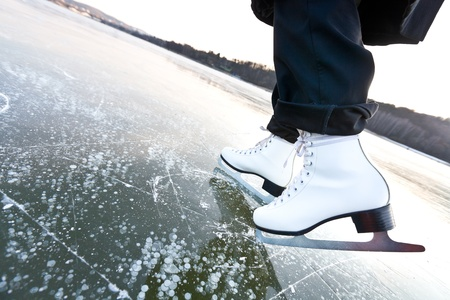ice dam: Woman ice skates with overview of a lake Stock Photo