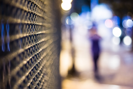 Mysterious night city, blurred figure and fence