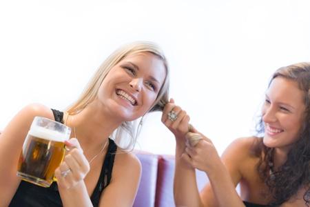 Two girls fighting over beer in restaurant photo