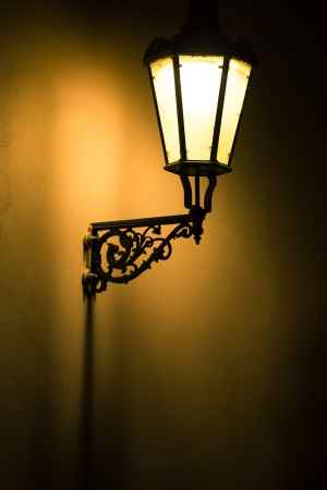 Dark moody picture of old lamp on the wall photo