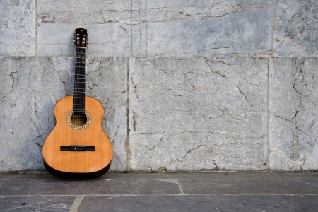 evoking: Single guitar left alone on a marble background  Shot evoking loneliness  Stock Photo