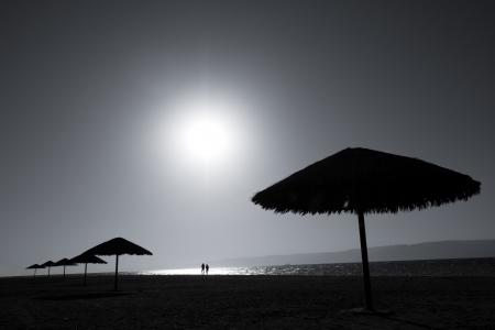 Due persone che camminano sulla spiaggia by the Sea Leggi.