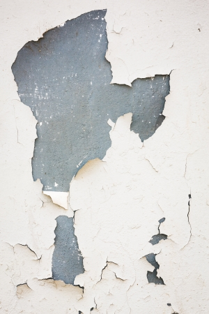 cracking: Old flaky white paint peeling off of a wall