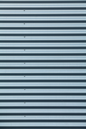 Tall shot of blue corrugated metal with bolts photo