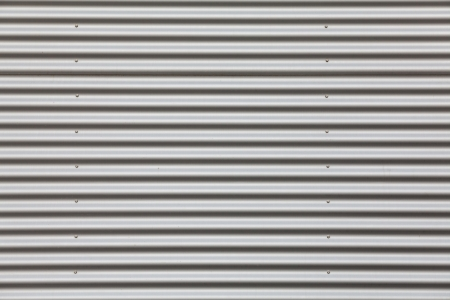 Wide shot of silver corrugated metal with bolts