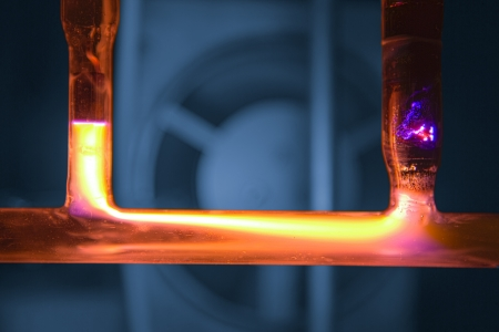 discharge: Yellow plasma discharge in tube, blue background with cooling fan