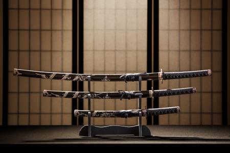 samourai: Katana, wakizashi et tanto sur le stand dans une pièce, fond jaune