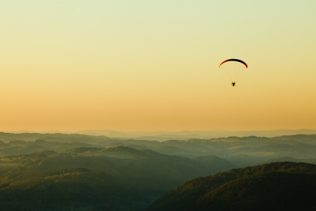 Moto paraglider above the landscape in sunset, copy space photo