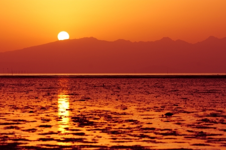 Sun is setting down above shallow sea waters and hills photo