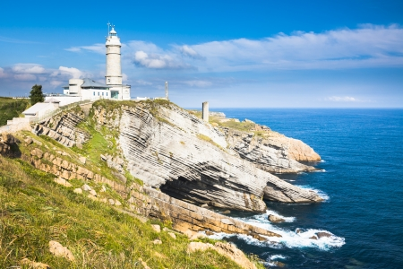cabo: The Cabo Mayor lighthouse near city of Santander, Spain, with cliffs, sky and sea