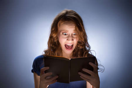 freaked: Concept shot of woman reading horror book nad screaming