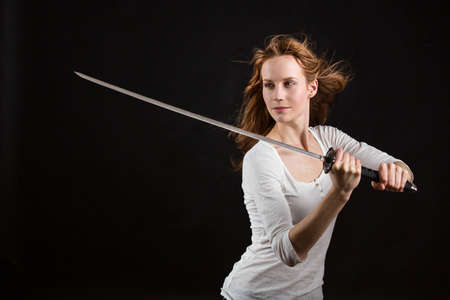 Beautiful woman with a sword, blade is slightly blurred Stock Photo