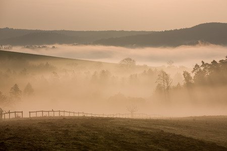 Foggy hills and valleys with fence in autumn dawn photo