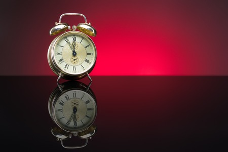 five to twelve: Vintage alarm clock showing five minutes to twelve, red background, copy space