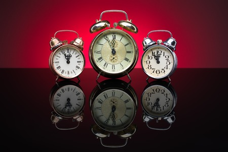 five to twelve: Vintage alarm clocks showing five minutes to twelve, red background