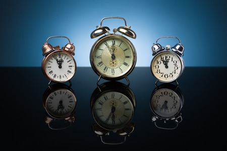 five to twelve: Vintage alarm clocks showing five minutes to twelve, blue background