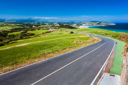 scenic drive: Road along the coast, Picos de Europa mountains in background Stock Photo