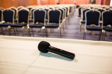 Horizontal shot of microphone and chairs in auditorium