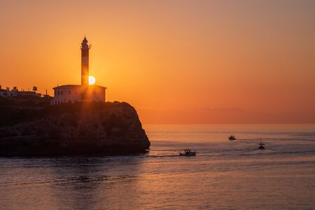 Sun is rising behind Porto colom lighthouse, boats going fishing, Mallorca