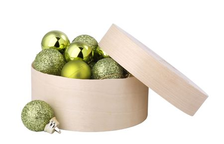 Green New Years balls in a round, wooden box. photo
