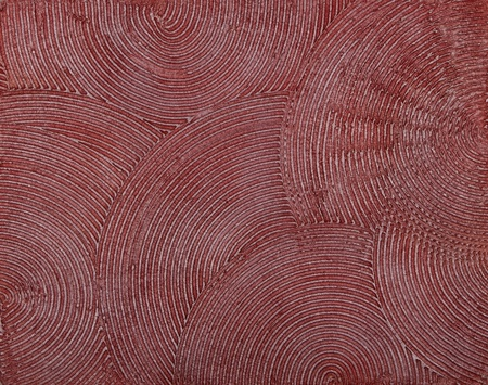 wall texture with a deep circular dabs of putty, covered with red paint.