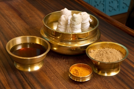 herbs powder and oil in bronze cups, prepared for  traditional indian ayurvedic  massage  photo