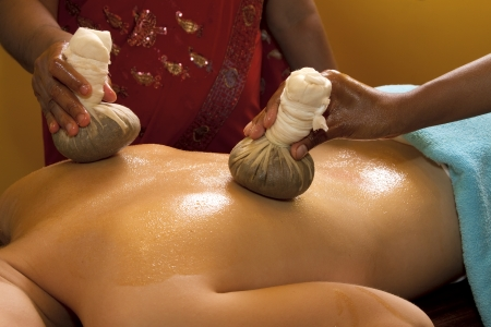 indian doctors doing traditional ayurvedic oil back massage photo