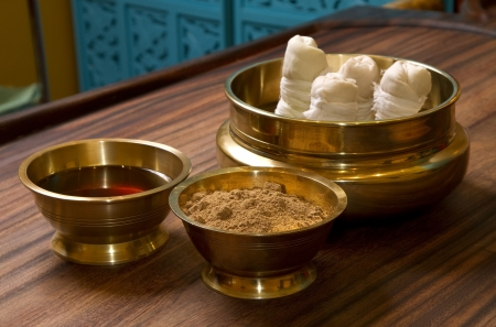herbs powder and oil in bronze cups, prepared for  traditional indian ayurvedic  massage