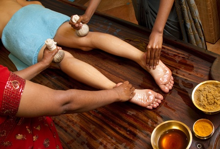 indian doctors doing traditional ayurvedic oil foot massage Stock Photo