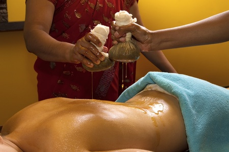 indian doctors doing traditional ayurvedic oil back massage