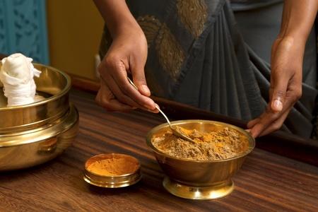 preparing herbs powder for  traditional indian ayurvedic  massage  Imagens