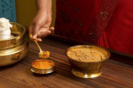 preparing herbs powder for  traditional indian ayurvedic  massage  photo