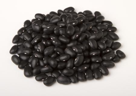 Haufen von schwarzen getrockneten Bohnen isoliert auf wei�.