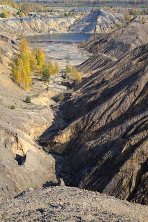 sand quarry: sand canyon with yellow autumn birches and a lake between hills Stock Photo