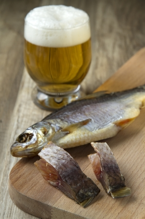 dried fish: salt dried fish and glass of beer on wooden background