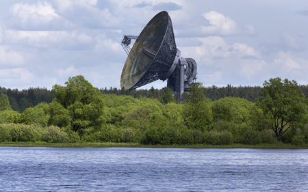 Huge satellite dish aimed at the sky, stands near river bank in Kaljazin, Russia.