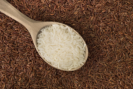White rice in a wooden spoon on red rice background