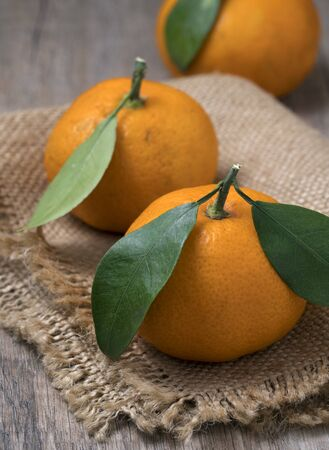 Fresh ripe tangerines with leaves in bowl on a wooden background. Close up view.
