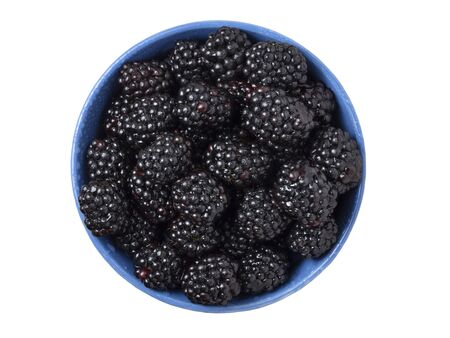 Ripe fresh blackberries in a bowl on white background. Top view. Stock Photo